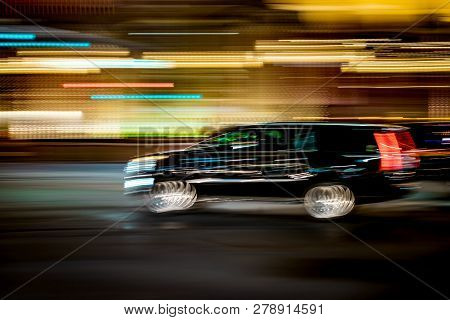 Black Suv Traveling Fast With Motion Blur And City Lights Concept