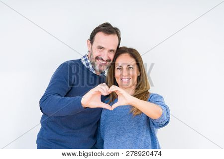 Beautiful middle age couple in love over isolated background smiling in love showing heart symbol and shape with hands. Romantic concept.