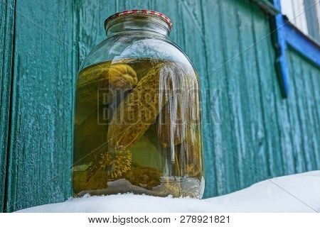 A Large Glass Jar Of Pickled Cucumbers On The Street In White Snow Against A Green Wall On The Stree