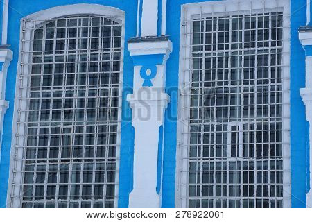 Two Old Iron Bars On The Blue White Wall Of The Building