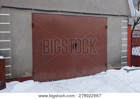 Brown Iron Gate On The Wall Of An Old Garage Outside In White Snow