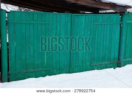 Green Wooden Rural Gate On The Street In White Snow