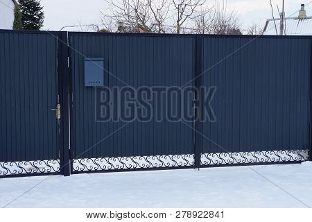 Gray Closed Metal Gates On The Street In White Snow
