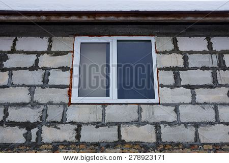 Large White Window On A Gray Brick Wall Of A Building