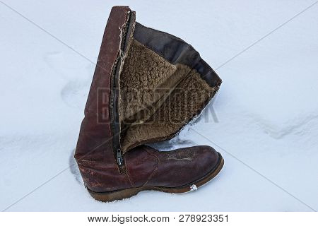 One Old And Dirty Brown Leather Boot Stands In A Snowdrift Of White Snow Outside