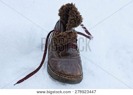 Old Brown Leather Boot With Fur Is Standing On White Snow