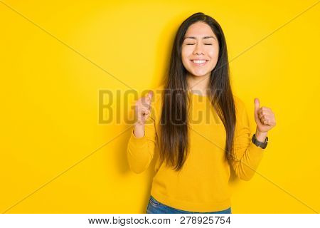 Beautiful brunette woman over yellow isolated background excited for success with arms raised celebrating victory smiling. Winner concept.