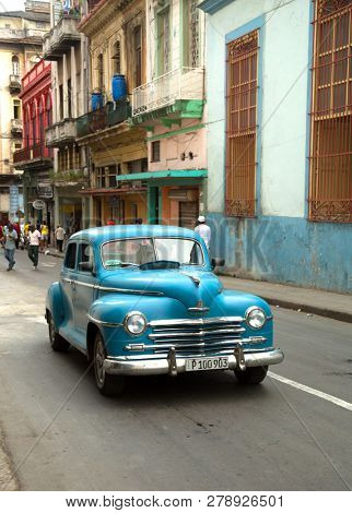 HAVANA-CUBA- DEC 4, 2018:  A classic American vintage car in turquoise and colonial architectural building in Old Havana in Cuba