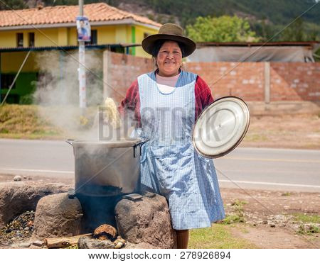 Peru village - 12 October 2018 : Woman cooking korn in saucepan on fire