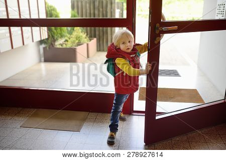Little Boy Opens The Door Of The Entrance And Holds It For His Parents. Independent Child