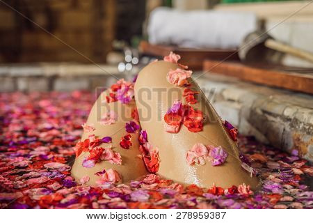 Attractive Young Woman In Bath With Petals Of Tropical Flowers And Aroma Oils. Spa Treatments For Sk