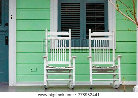 Two White Rocking Chairs On Porch Of Green New Orleans American Home