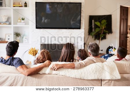 Back view of three generation Hispanic family sitting on the sofa watching TV