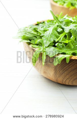Fresh Green Arugula Leaves On Wooden Bowl, Rucola Salad On White Wooden Rustic Background With Place
