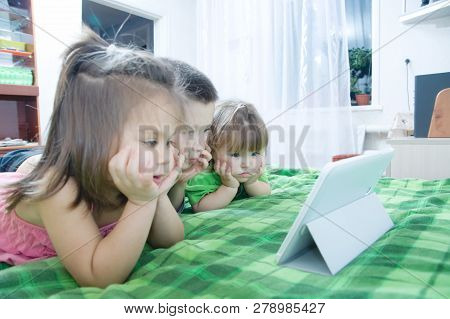 Children Looking On Pad Lying On Bed At Home. Children Time Spending. Kids Using Tablet Computer