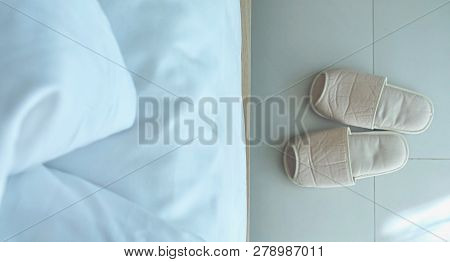 A Pair Of Slipper Shoes Are Beside The Bed In The Minimal Room Style, Close-up Of Slipper On The Flo
