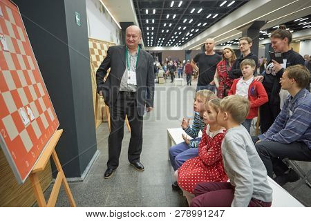 ST. PETERSBURG, RUSSIA - DECEMBER 27, 2018: Three-time world champion for chess composition Oleg Pervakov gives a lesson to children during World Rapid and Blitz Chess Championship 2018