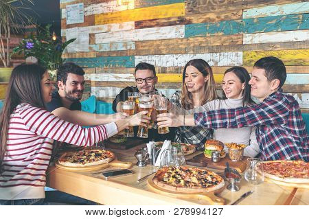 Happy Young Hipster Friends Celebrating By Toasting With Beer Eating Pizza And Burgers At Bar Restau