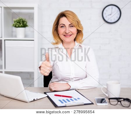 Business And Success Concept - Happy Mature Business Woman Thumbs Up In Modern Office