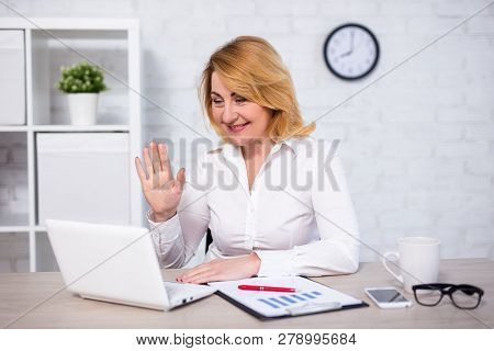 Video Conference Concept - Portrait Of Mature Business Woman Sitting In Office With Laptop And Talki