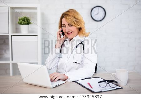 Cheerful Mature Woman Doctor Or Nurse Working With Laptop And Talking By Phone In Modern Office