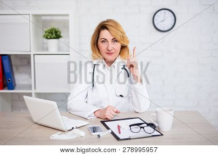 Potrtait Of Serious Mature Female Doctor Showing Attention Sign In Modern Office