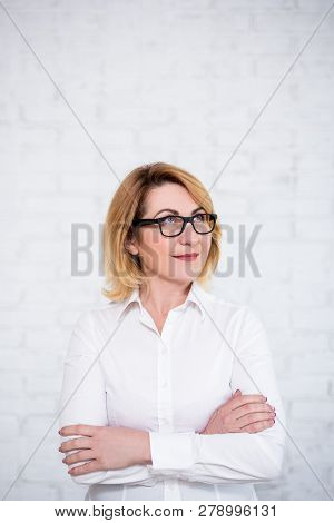 Idea Concept - Mature Business Woman In Eyeglasses Looking Up Ant Thinking About Something Over Whit