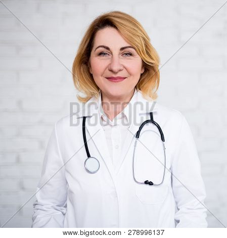 Portrait Of Mature Woman Doctor Posing Over White Brick Wall