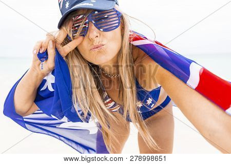 Woman Aussie Supporter, Travel Or Tourism.  Female Draped In Australian Flag Hand Sign V And Pursed