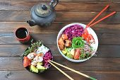 Organic food. Fresh seafood recipe. Two fresh poke bowls with salmon, shrimps, rice, red cabbage, avocado, cherry tomatoes and radish sprouts on wooden background. Food concept Poke Bowl poster
