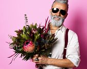 Handsome older stylish bearded man in white shirt holding a bouquet of flowers over pink background and looking at camera in sunglasses poster