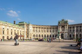Wien / Austria -  October 10 2014: Tourist on a segway near the statue of Prince Eugene against  Neue burg,  the new part of the Hofburg palace in historical part pf Vienna