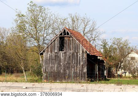 Abandoned Old Wooden Barn With Broken Dilapidated Wooden Boards Next To Unused Paved Parking Lot Sur