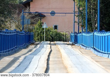 Partially Renovated Wavey Old Wooden Bridge With New Blue Metal Frame On Each Side And Strong Suppor