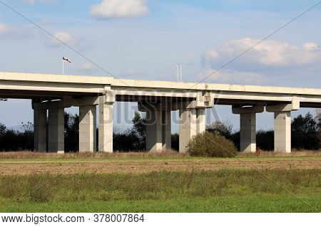 Side View Of Wide Concrete Bridge On Top Of Multiple Strong Thick Support Columns With Dirty Old Win