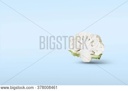 One Half A Head Of Cut Cauliflower Closeup Levitate In The Air On A Blue Background With A Shadow. C