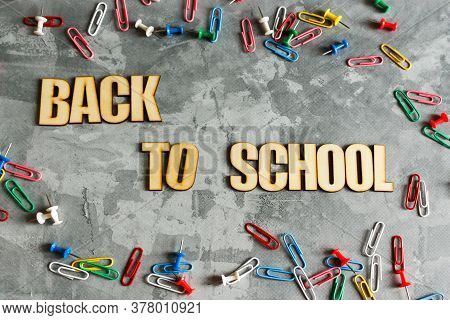 Inscription Back To School With School Supplies On Gray Concrete Background. High Quality Photo