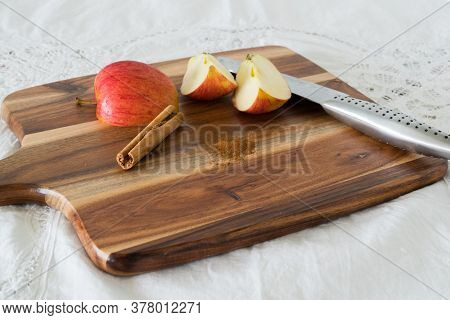 Wedges Of Apple With Cinnamon Stick And Ground Cinnamon On Wooden Chopping Board