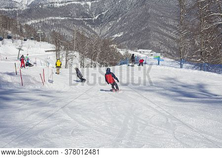 Snowboarders On A Snowy Slope. Mountain Ski Resort. A Place To Ride On The Board. People Go Down The