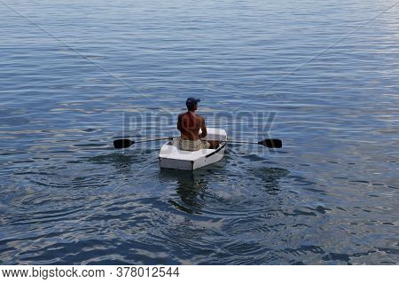 Salvador, Bahia / Brazil - March 21, 2013: Man Is Seen Rowing A Small Boat Across The Waters Of Baia