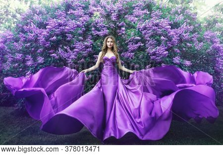 Fashion Model In Lilac Flowers, Young Woman In Beautiful Long Dress Waving On Wind, Outdoor Beauty P