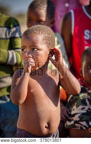 happy African boy sucking his thumb together with his friends in a  village in Botswana