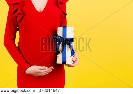 Cropped Image Of Pregnant Woman In Red Dress Holding A Gift Box And Touching Her Belly At Yellow Bac
