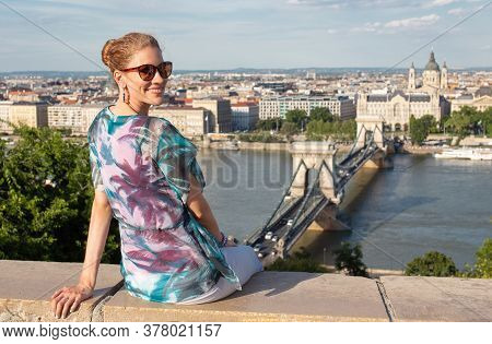 Happy Young Redhead Caucasian 20s Woman Sit And Toothy Smile At Budapest Panorama, Hungary