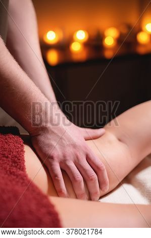 Close-up Professional Massage Of The Female Hip In The Dark Room Of The Spa Salon Against The Backgr