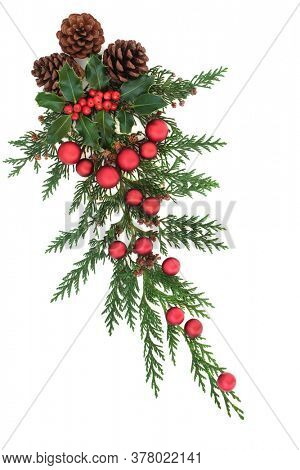 Christmas decoration with holly, cedar cypress, pine cones & red baubles on white background. Decorative xmas element for the festive season. Flat lay, top view.
