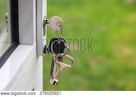 A Bunch Of Keys In A Lock In An Open White Door Of A House On A Blur Background Of A Garden With Cop