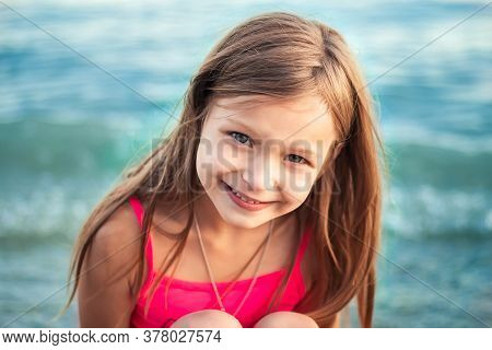 Close-up Portrait In A Sunset Light Of A Pretty Happy Caucasian Girl With Long Hair, Cute Eyes And A