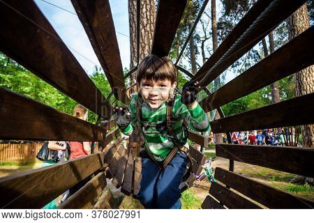 Little Boy Playing At Rope Adventure Park. Summer Holidays Concept. Cute Child Having Fun In Net Tun