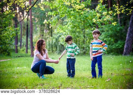 Young Woman Mother Applying Insect Repellent To Her Two Son Before Forest Hike Beautiful Summer Day